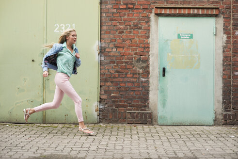 Running young woman in front of industrial building - LFOF000170