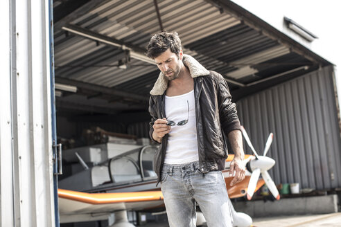 Man with leather jacket standing in front of propeller plane in hangar - MUMF000018