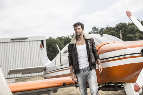 Man with leather jacket standing in front of propeller plane - MUMF000021