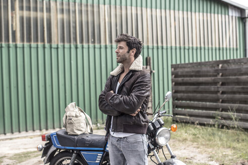 Portrait of man waiting in front of motorcycle - MUMF000034