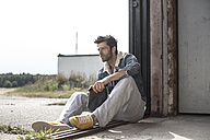 Man sitting on ground watching something - MUMF000026