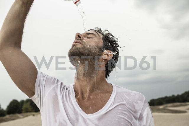 Portrait of man pouring water from bottle over himself - MUMF000048