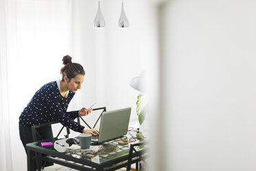 Young woman working with laptop at home - EBSF000124
