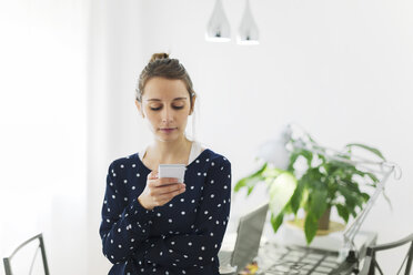 Young woman reading SMS on smartphone at home - EBSF000146