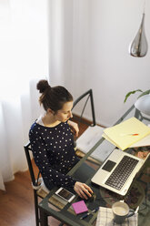 Young woman working with laptop at home - EBSF000136