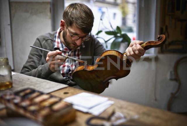 Violin maker in his workshop varnishing repaired violin - DIKF000082