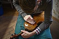 Violin maker polishing repaired violin - DIKF000099
