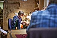 Violin maker in his workshop restoring a scroll - DIKF000116