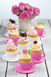 Baking dishes formed like cups with decorated cupcakes and roses on wooden table - CSF021174