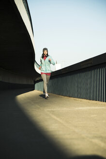 Young female jogger on the move on a bridge - UUF000101
