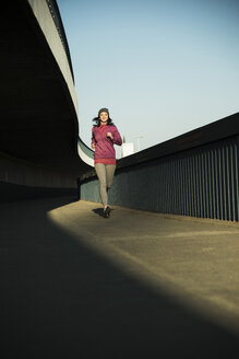 Young female jogger on the move on a bridge - UUF000103