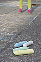 Little girl playing hopscotch, coloured crayons lying in the foreground - YFF000079