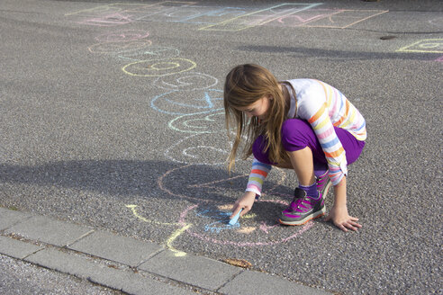 Girl drawing with coloured crayon on asphalt - YFF000082