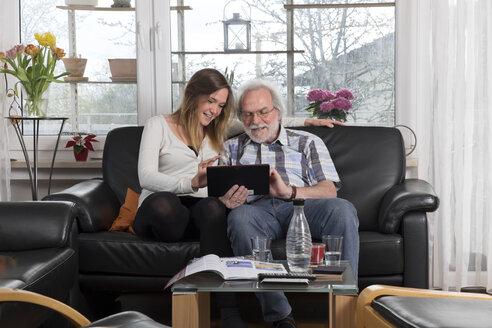 Young woman explaining digital tablet to senior man - LAF000694