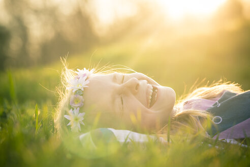 Portrait of laughing little girl lying on meadow wearing flowers - SARF000430