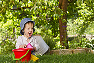 Toddler playing with sandbox toy in the garden - LVF000990
