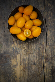Bowl of kumquats on wooden table - LVF000982