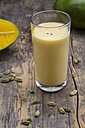 Glass of mango lassi and cardamom capsules on wooden table - LVF000980