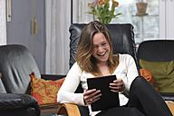 Young woman having fun with tablet computer at home - LAF000719