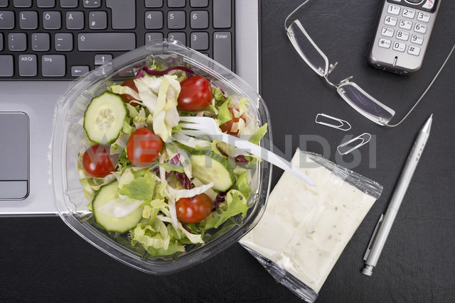 Workplace with mixed salad on laptop - CSTF000216