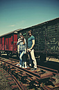 Three friends with sunglasses standing in front of old freight car - HOHF000663