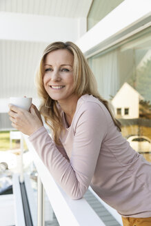 Portrait of woman with a cup of coffee leaning on railing - MFF000960