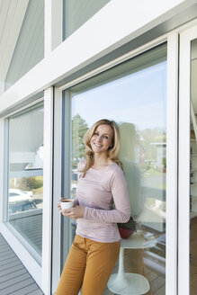 Woman with a cup of coffee leaning at glass front of her house - MFF000963