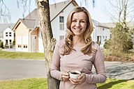 Smiling woman with cup of coffee standing in front of residential area - MFF000968