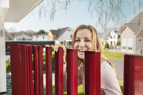 Smiling woman standing behind red fence of residential house - MFF000981