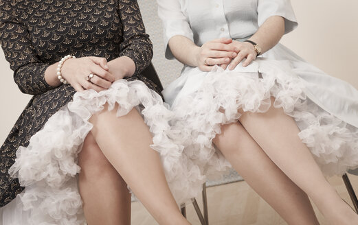 Young women in vintage dresses sitting side by side - DISF000758