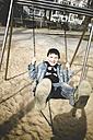 Boy laughing, on swing on playground, Dusseldorf, North Rhine-Westphalia, Germany - SBD000733