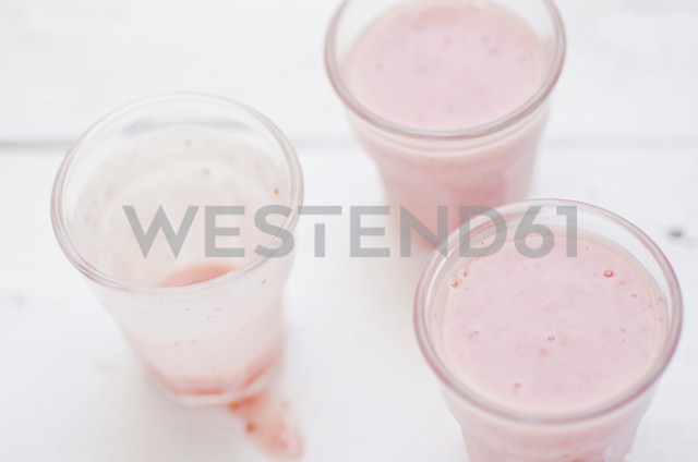Two glasses of banana strawberry buttermilk shake and one with leftovers on white wooden table - CZF000145