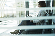 Business woman using tablet computer while waiting on platform - UUF000122