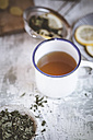 Cup of peppermint ginger tea and dried peppermint leaves in bowl - SBDF000758