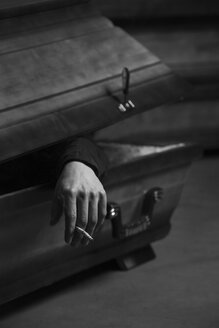 Hand with cigarette stub hanging out of opened coffin - CvK000072