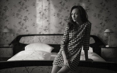 Woman in dress leaning against bed - CvK000104