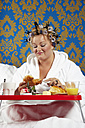 Woman with curlers and white bathrobe having breakfast in bed - CSBF000006