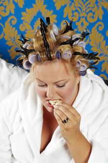 Portrait of woman with curlers and white bathrobe having breakfast in bed - CSBF000009