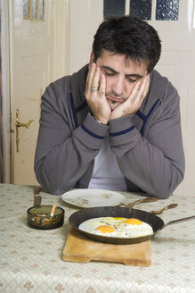 Portrait of man with bad habit sitting at breakfast table - CSBF000015