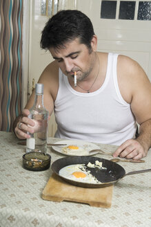 Portrait of man with bad habit sitting at breakfast table - CSBF000018