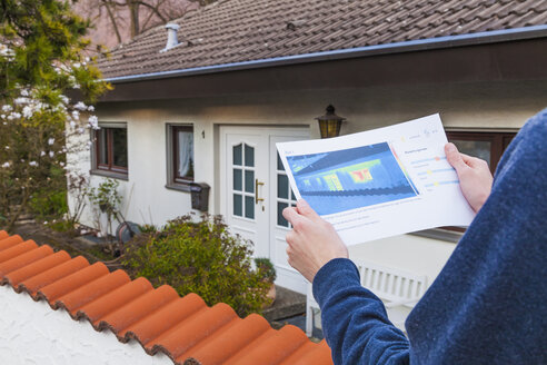 Germany, Geislingen, Person holding thermography of building - WDF002453