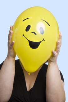 Woman holding balloon with smiley face in front of her face - CSB000031