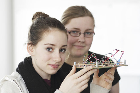 Two young women holding component an optical sensor in an electronic workshop - SGF000545