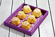 Muffins and baking decor on purple wooden tablet - CSF021204