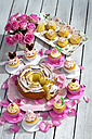 Birthday cake, cupcakes, muffins and flower vase of pink roses on wooden table - CSF021210