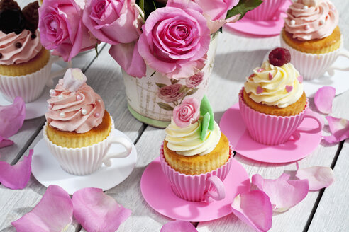 Cupcakes and flower vase of pink roses on wooden table - CSF021213