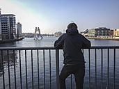 Germany, Berlin, Elsen bridge, young man looking at Spree with molecule man - FBF000336