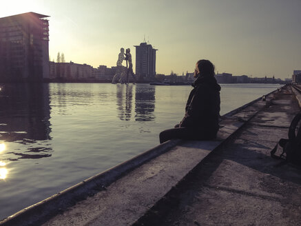 Germany, Berlin, Treptow, young man sitting on pier at sunset - FBF000340
