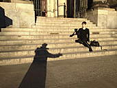 Germany, Berlin, dome of woman on stairs, preparing for handshake with shadow of man - FBF000321