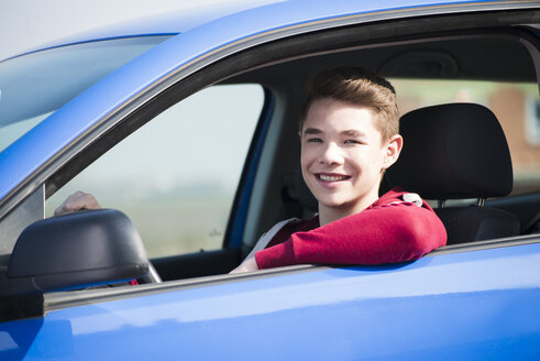 Teenager sitting in car, partial view - UUF000173